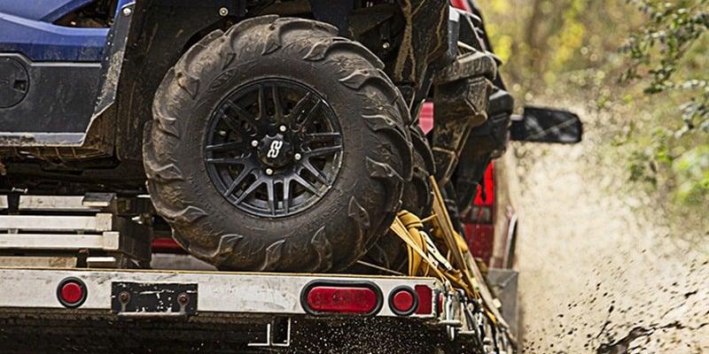 Truck hauling UTV on trailer through mud