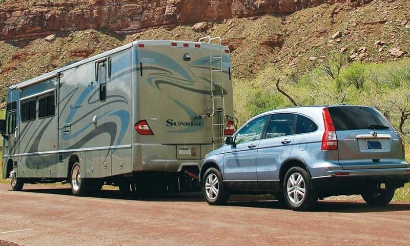Large RV flat towing Honda CRV in Desert setting