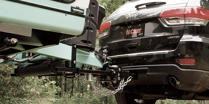 Jeep Cherokee towing camper and connected by Curt trailer hitch