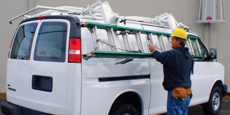 Man placing ladder into ladder rack attachment on work van