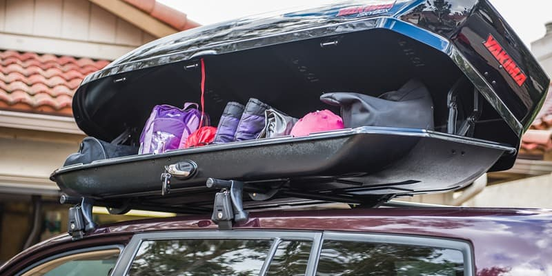 Yakima Rooftop Skybox cargo carrier full of ski gear on Burgundy SUV