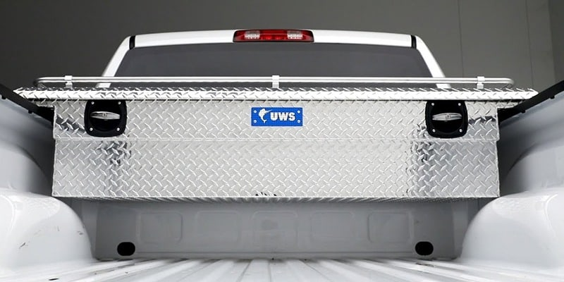 Metal UWS tool box in bed of white truck
